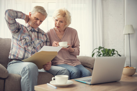 Portrait of confused elderly couple focused on paper with testament. Copy space in right side