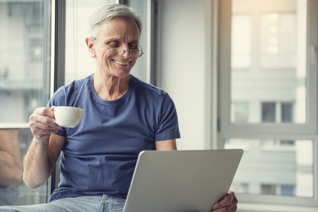 Portrait of content retired man sitting near window. He is holding cup of hot beverage and staring at computer screen with delight