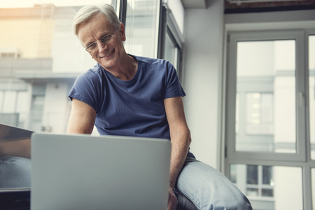 Portrait of elderly male person relaxing on windowsill in front of notebook and smiling while looking at screen. Copy space in right side