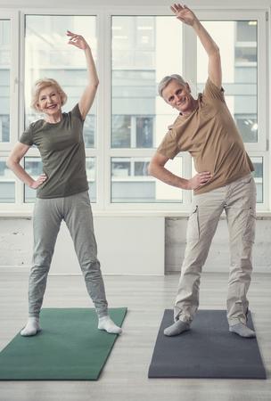 Attività fisica. Ritratto integrale delle coppie felici di invecchiamento che stanno sui tappeti con le armi alzate. Ampia finestra sullo sfondo Archivio Fotografico