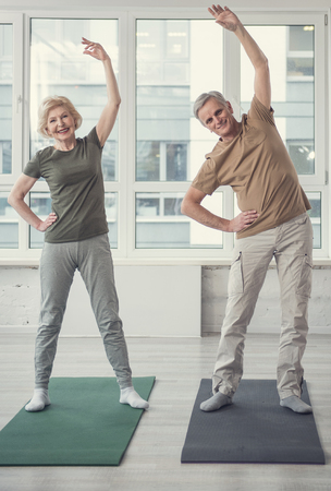 Physical activity. Full length portrait of happy aging couple standing on carpets with raised arms. Wide window on background