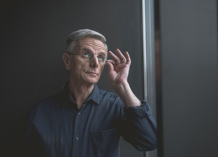 Portrait of pensive old businessman holding eyeglasses by arm indoor. Inspiration and reverie concept
