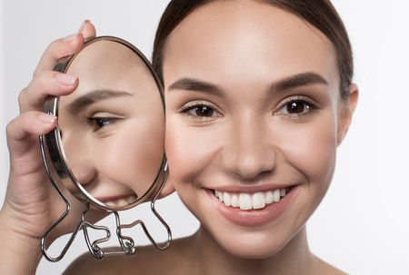 Natural attractiveness. Close up portrait if positive delighted young woman is standing and holding mirror near her face while reflected in it. She is looking at camera with joy. Isolated background