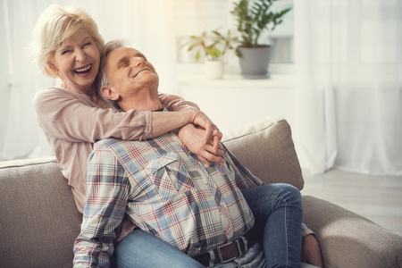Satisfied pensioners relaxing on sofa. Woman sitting behind male back and embracing him with hands and legs