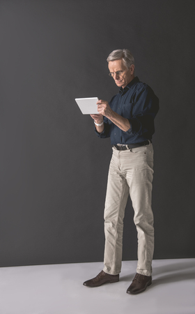 Full length portrait of serious old businessman typing in electronic tablet while keeping it in arms. Career and technology concept
