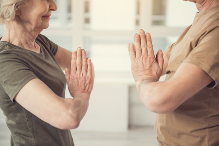 Joyful senior woman and man standing with clasped hands and looking at each other with smile