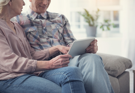Progressive pensioners. Mature wife and husband spending weekend with tablet. They are calm and satisfied Imagens