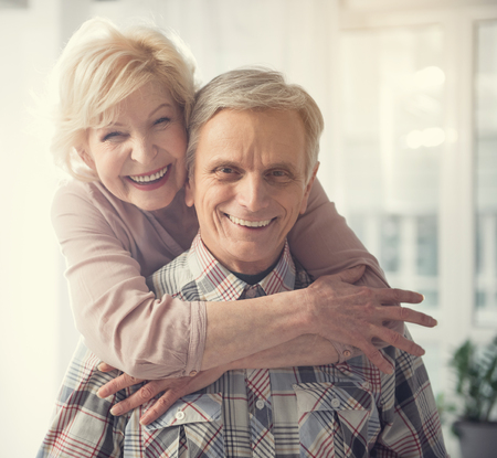 Happy old age. Portrait of hugging pensioners looking at camera with broad smile