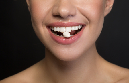 Close up of mouth with white healthy teeth of positive young woman. She is enjoying chewing gum. Isolated on dark background. Fresh breath concept Stock Photo