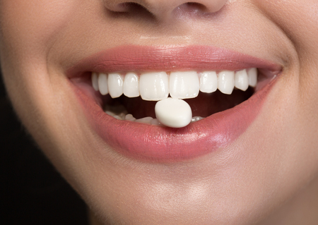 Joyful girl is showing white healthy teeth with chewing gum into mouth. Fresh breath concept. Close up