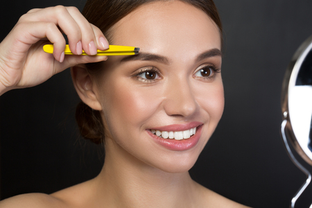 Portrait of delighted attractive girl is plucking eyebrows with smile. She is standing and using tweezers while looking at the mirror. Isolated background