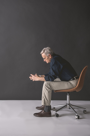 Full length side view thoughtful retire male sitting on cozy chair. Reverie concept Stock Photo