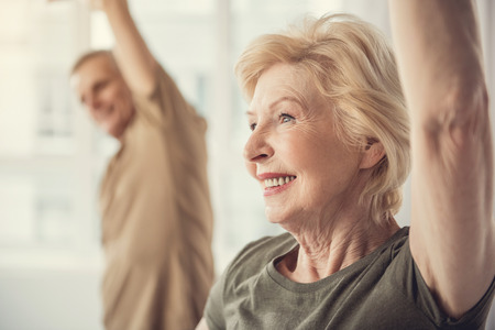 contented senior female standing with raised arm. Male on background. Focus on woman Stock Photo