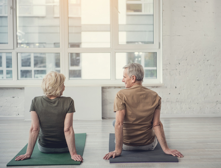 Tranquil old male and woman sitting with their backs on carpets with their back to camera and looking at each other Stock Photo