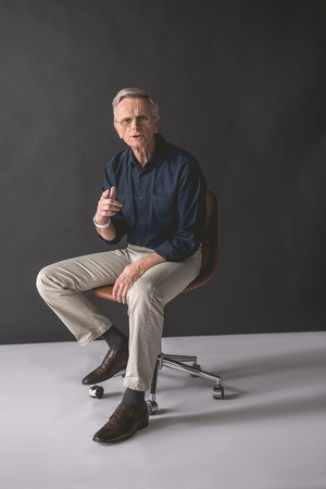 Hey you. Full length portrait of dissatisfied old businessman pointing finger while locating on chair. Indignation concept Imagens - 98977858