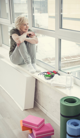 Happy senior lady sitting on windowsill with her legs tucked up and smiling. Copy space in right side Stock Photo