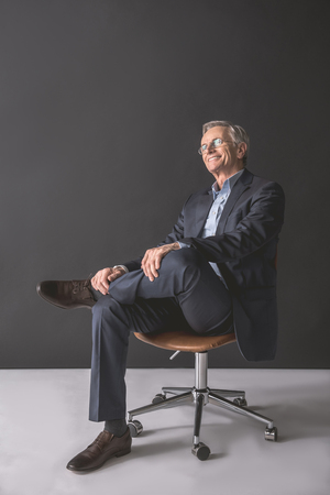 Full length portrait of cheerful old businessman relaxing on chair. Leisure during labor concept Standard-Bild