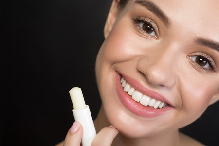 Close up portrait of cheerful attractive young woman is looking at camera with joy while holding hygienic lipstick. Beauty concept. Isolated background