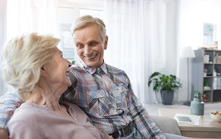 Delighted senior man and woman hugging on sofa and looking each other with fondness. Copy space in right side