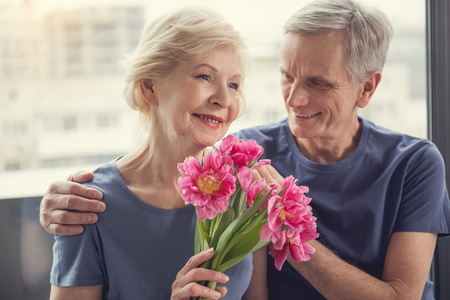 Glad husband hugging his darling by the shoulders with delicacy. Woman holding flowers and smiling Stock Photo