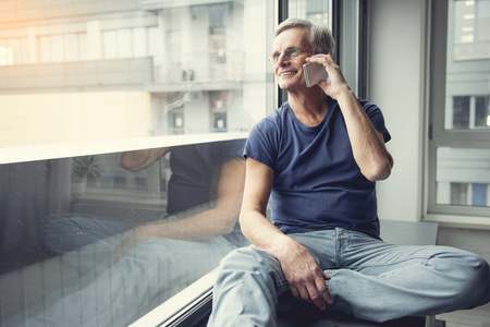 Enjoyed mature man relaxing near window and having pleasant conversation by mobile phone. Copy space in left side