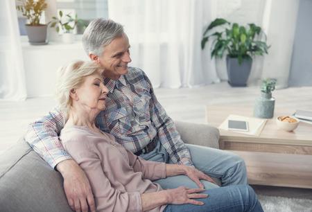 平和的な退職。アパートで居心地の良いディバンでリラックス成熟した夫と妻。抱きしめて静かにしている 写真素材