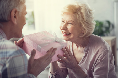 Senior female person with satisfied face taking present box which husband passing her Zdjęcie Seryjne