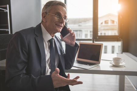 Is it really. Portrait of outgoing old businessman chatting by phone while gesticulating arms. He sitting at table. Communication by gadget during job concept Imagens