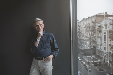 Portrait of thoughtful mature male keeping chin by hand while leaning against wall inside. Wistful employer concept Reklamní fotografie