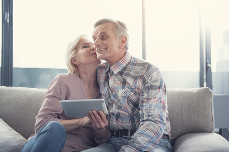 Love forever. Happy elderly woman with tablet in hand kissing her husband while sitting in living room