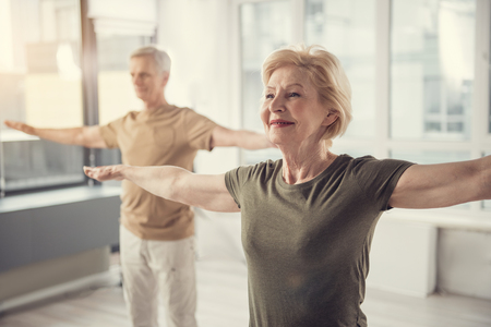 Waist up portrait of old jolly lady with arms straightened out aside. Male pensioner in same posture standing on background. Focus on woman Standard-Bild