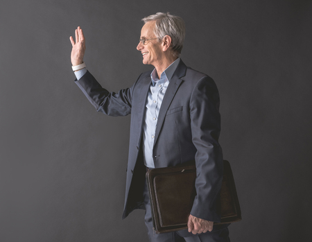 Side view happy senior male gesticulating hands while holding bag in arm. Pleased retire greeting concept Banco de Imagens
