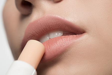 Close up low angle of sensual mouth of pensive young woman is applying hygienic lipstick. Beauty concept