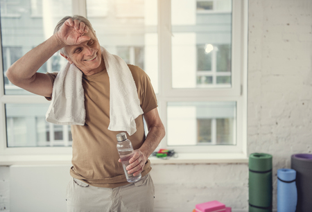 Smiling old male standing with bottle of water and wiping his forehead with hand. Copy space in right side