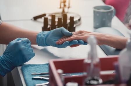 訪問者のためのマニキュアを作成するネイルアーティストの手を閉じます。彼らは美容院のテーブルに座っている。職業コンセプト