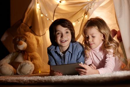 プレイルームでモダンなタブレットを使用して子供たちを楽しみます。彼らはじゅうたんの上におもちゃのテントに横たわっていた。幸せでカメラ