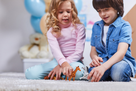 Joyful boy and girl with great relish have fun in children room. Focus on figures of wild animals Stock Photo