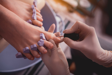 Top view close up female manicurist hand in gloves painting nails on feet of lady. Treatment concept Stok Fotoğraf