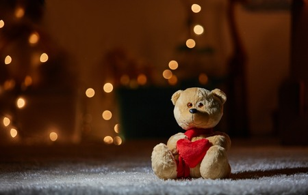 Focus on plush bear in nice red scarf holding soft heart. It is sitting on the floor. Copy space Stock Photo
