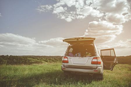 夏の牧草地で車のトランクの観光機器。家族旅行のコンセプト。スペースのコピー
