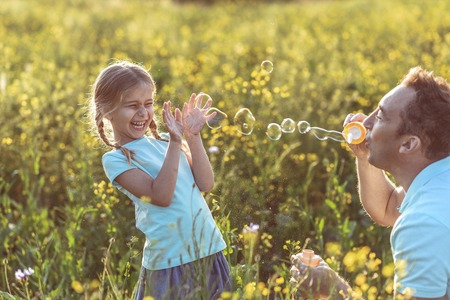 Joyful father is blowing soap bubbles in front of his laughing daughter. They are playing on summer meadow