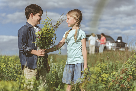 Cheerful boy is giving bouquet of wild flowers to girl. They are looking at each other and smiling. Their parents are standing on background