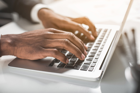 Modern device. Close up of hands of young african businessman is sitting at table and typing on laptop. Selective focus Stock Photo