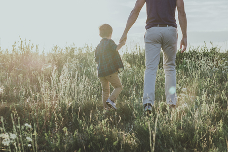 little boy standing on grass and holding his dad by hand. Copy space in left side