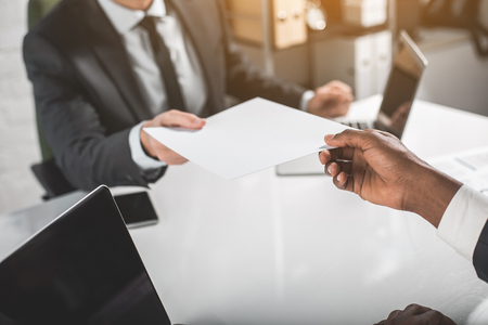 Take it. Close up of hand of african businessman is sitting at table and holding sheet of paper together with his colleague. Selective focus Reklamní fotografie