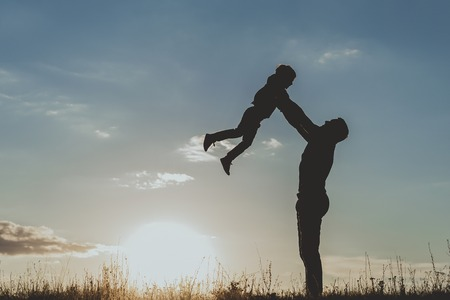 Side view profile of adult male silhouette standing on grass and holding up little boy in outstretched arms against sundown sky background. Copy space in left side Stock Photo
