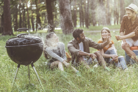 Focus on grill with smoke. Men and women sitting on background and talking while waiting for food