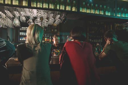 Sereno barista che serve clienti soddisfatti. Tornano alla telecamera. Uomo concentrato che ha lavoro nel concetto del pub