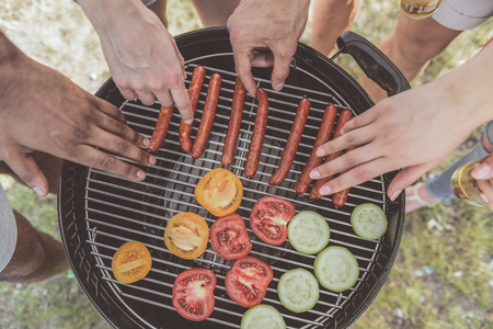 male and female hands taking grilled sausages and vegies from barbecue. Top view close up