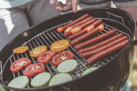 barbecue grate with vegetable and sausages on it. Friends standing nearby. Close up